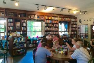Enjoying book and food at Storieville. Photo Credit: M'Lissa Howen.