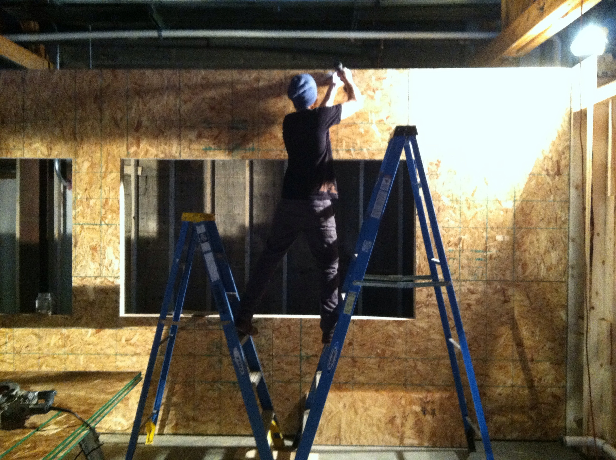 Joe Sheehan installing 5/8ths OSB on north side of hallway. (Two ladder man)