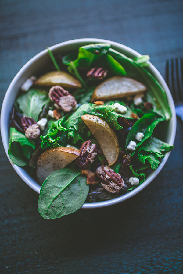 A classic fall salad perfect for Thanksgiving consisting of baby leafy greens, bacon crumble, candied pecans, goat cheese, and asian pears topped off by a delicious vinaigrette.   insolenceandwine.com