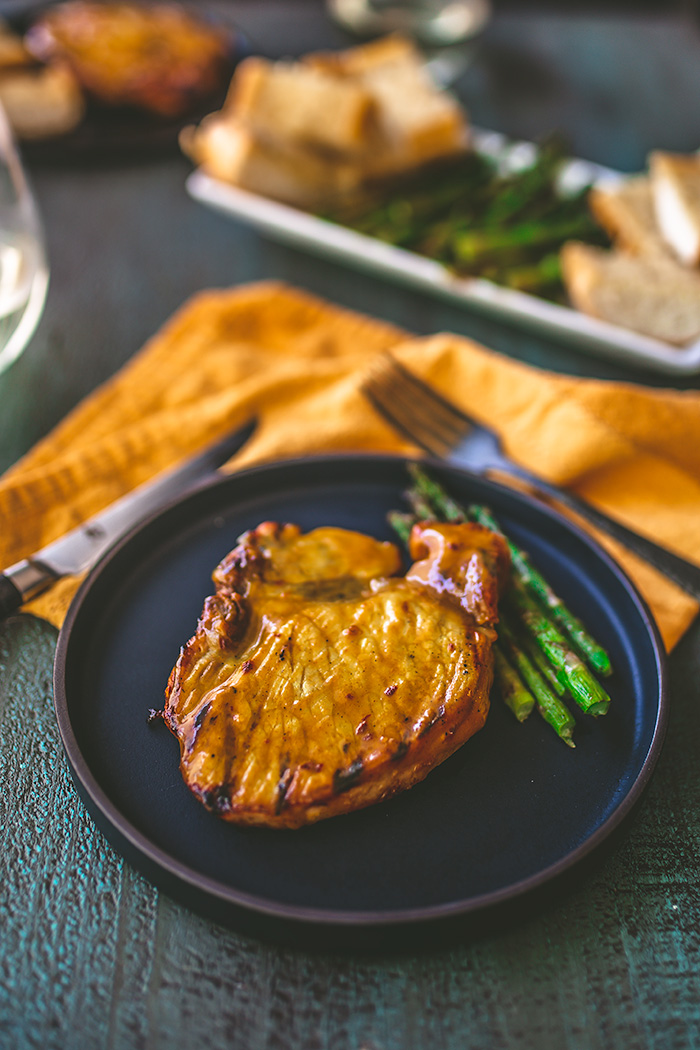 Inspired by Hawaiian-flavors, bone-in pork chops are grilled on a Traeger grill, and coated with a bright pineapple-ginger glaze. Serve with garlic bread.