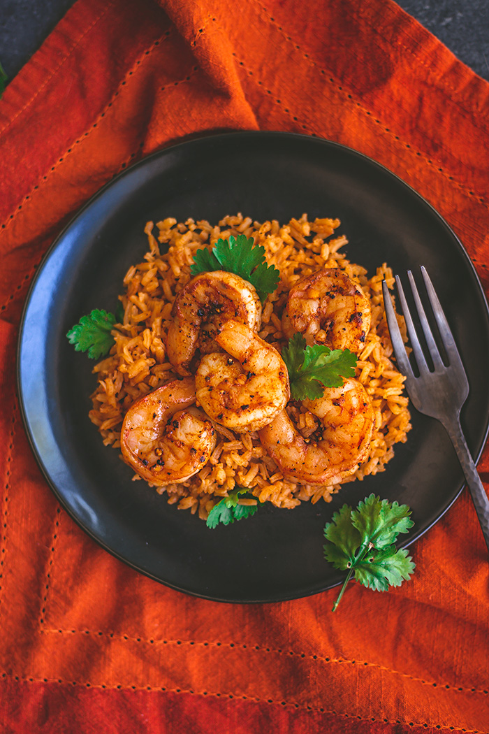 Grilled spicy Spanish grilled shrimp are delicious served over a bed of Spanish rice paired with a Spanish varietal of wine.