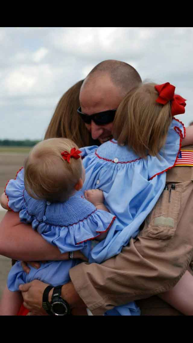 Family giving hugs while Reconnecting from an overseas deployment.