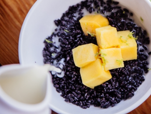 Hot puffed black rice with fresh mango, and warm sweet coconut milk