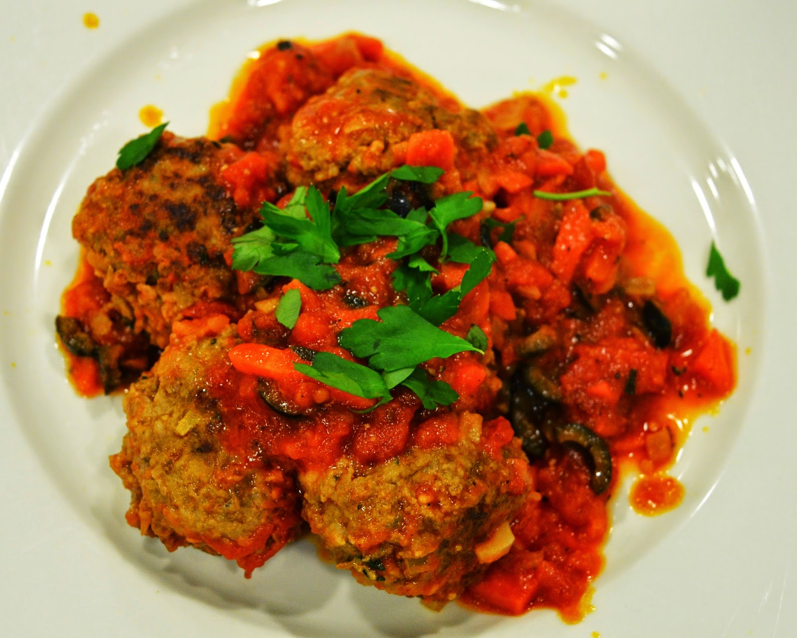 Queen olive-stuffed beef meatballs with tomato and olive sauce
