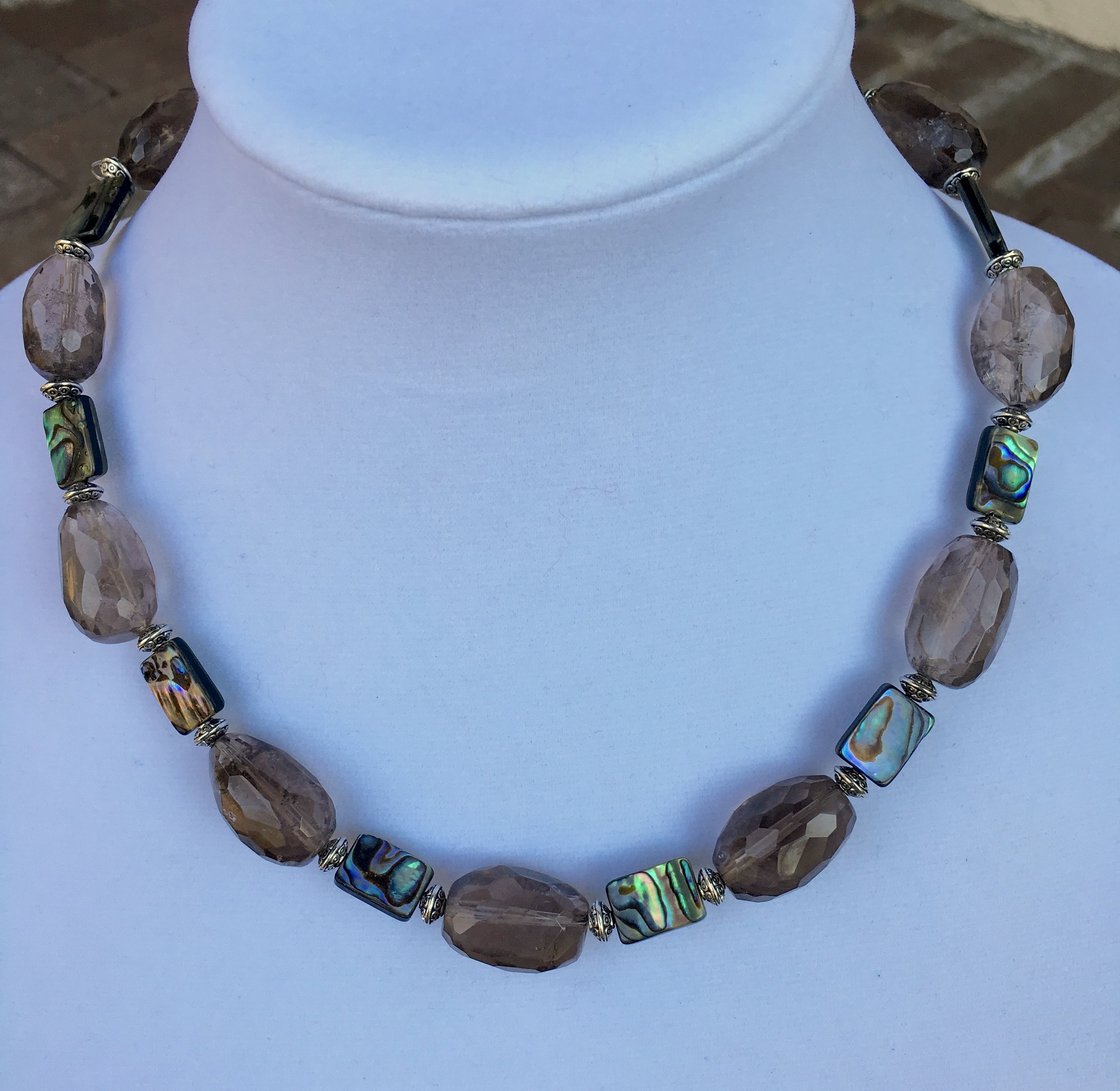 smoky quartz with abalone necklace  12 x 24 mm faceted oval smoky quartz beads. 10 x 14mm rectangular abalone beads. Silver plated beads. Sterling silver clasp. 20 in. $175