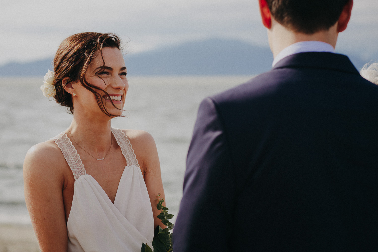 bride with hair blowing in her face on the beach