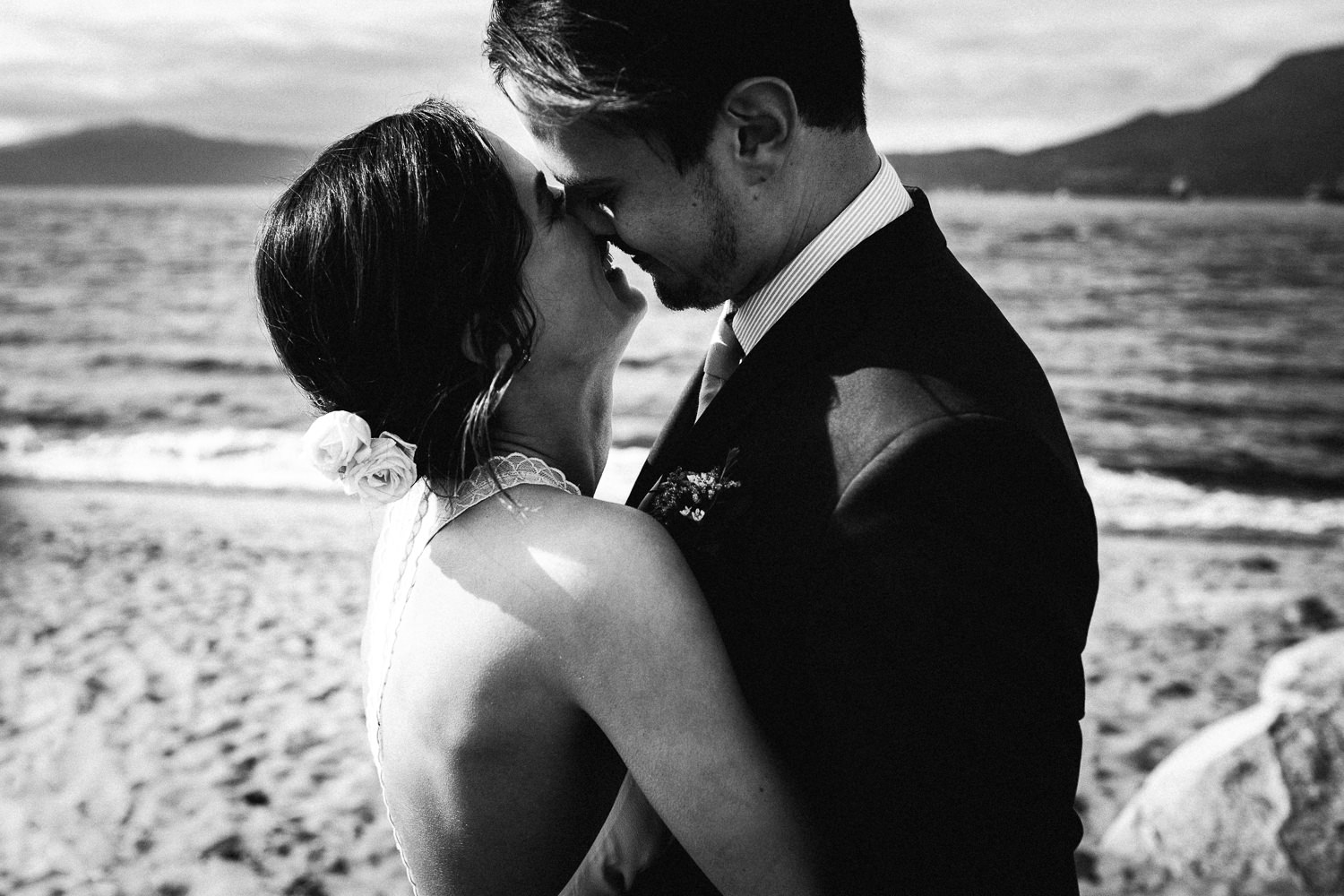 bride and groom canoodling on the beach
