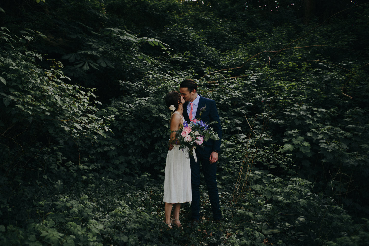 beautiful bride and groom surrounded by green