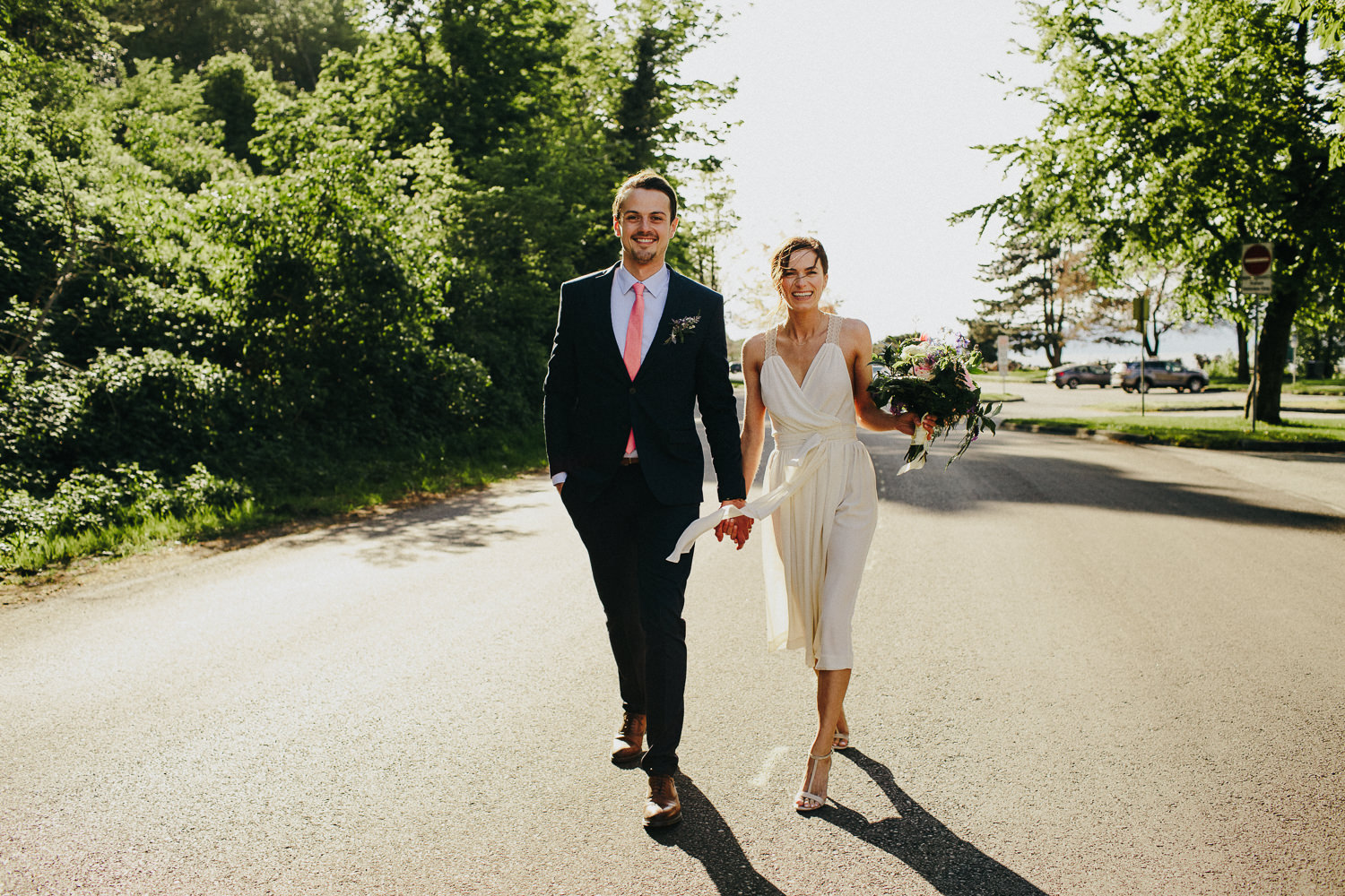 bride and groom walking on the road in spanish banks