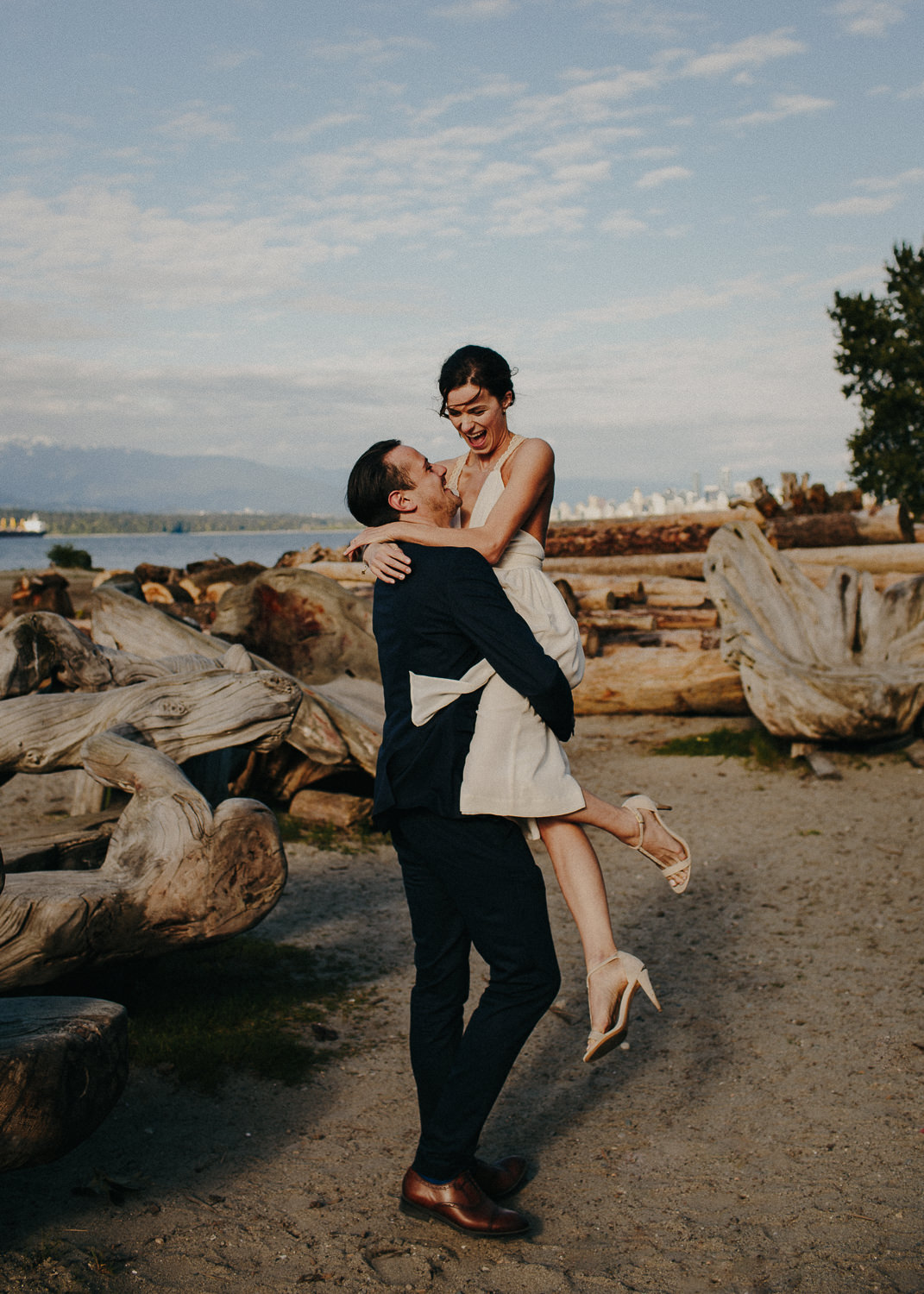 bride laughing as groom lifts her up