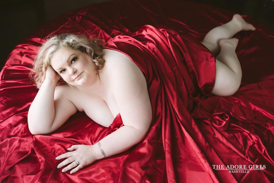 The Adore Girls Boudoir Photography Nashville red sheet smile
