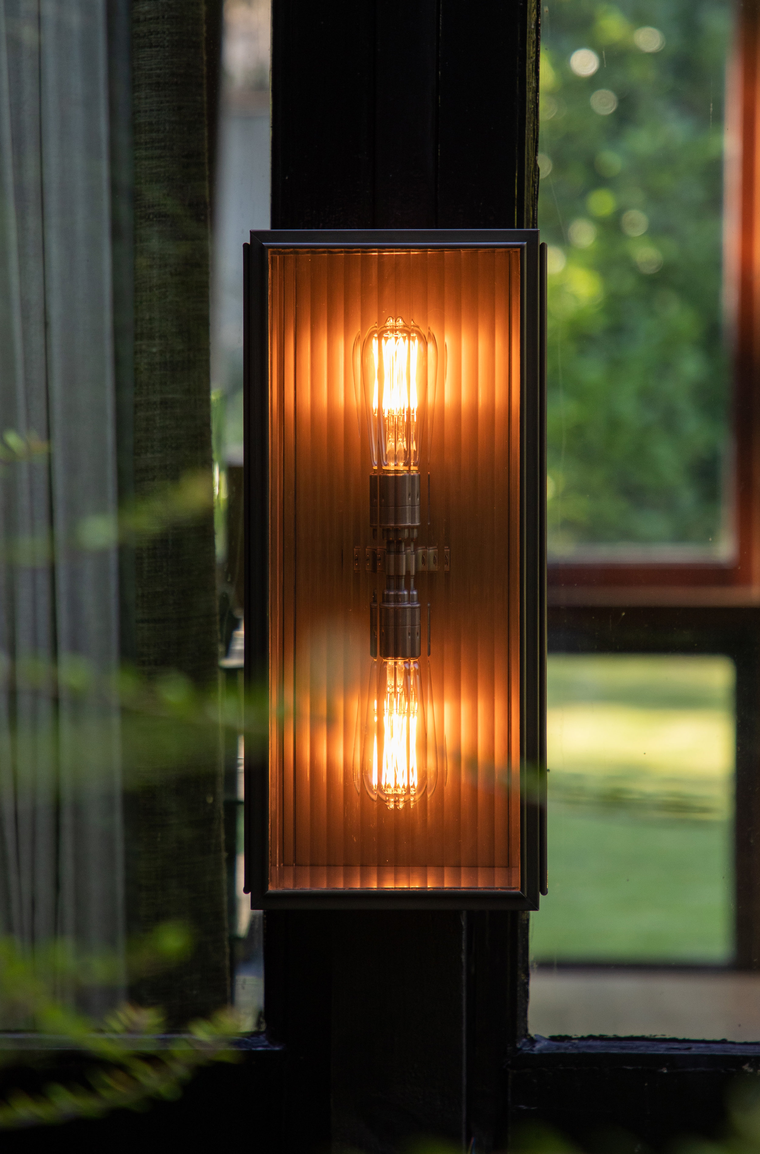 Unique Glazing Options - Our lantern collection is now available with reeded glass (as well as our standard clear or frosted options). The vertical reeds refract and diffuse the light source and givi a more architectural feel to the aesthetic of the light.Shown: Large Birch Wall Light - twin lamp version in Bronze