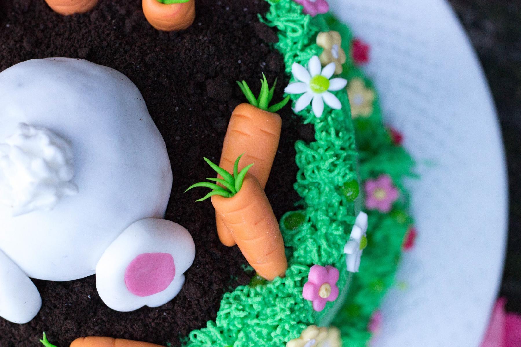 Ostertörtchen mit Hasen und süßen Karotten in einer Blumenwiese