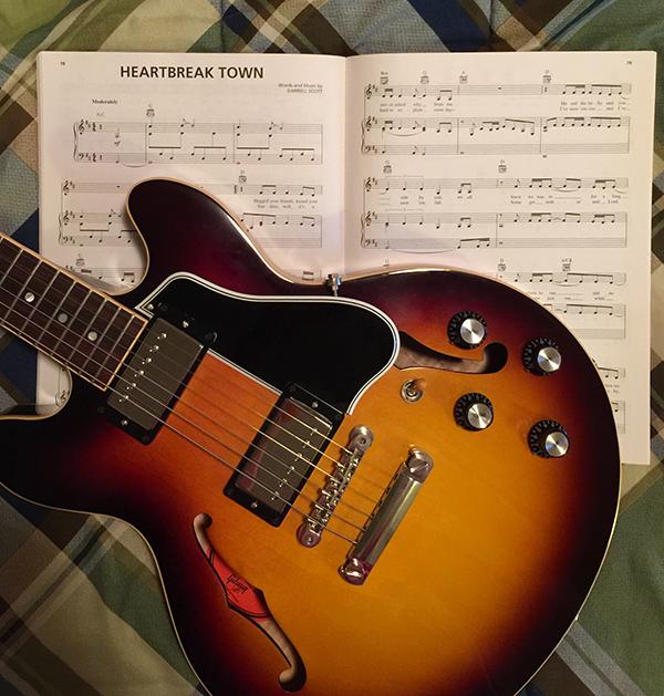 Elissa enjoys playing 'Heartbreak Town' on her guitar.