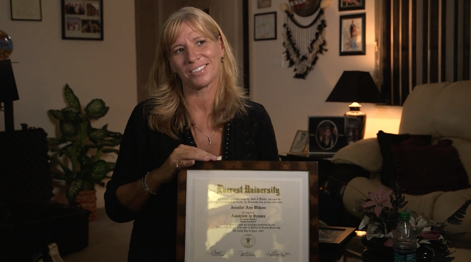"""Fail State Student Jennifer Wilson holding her """"worthless"""" diploma from now-defunct Everest University."""