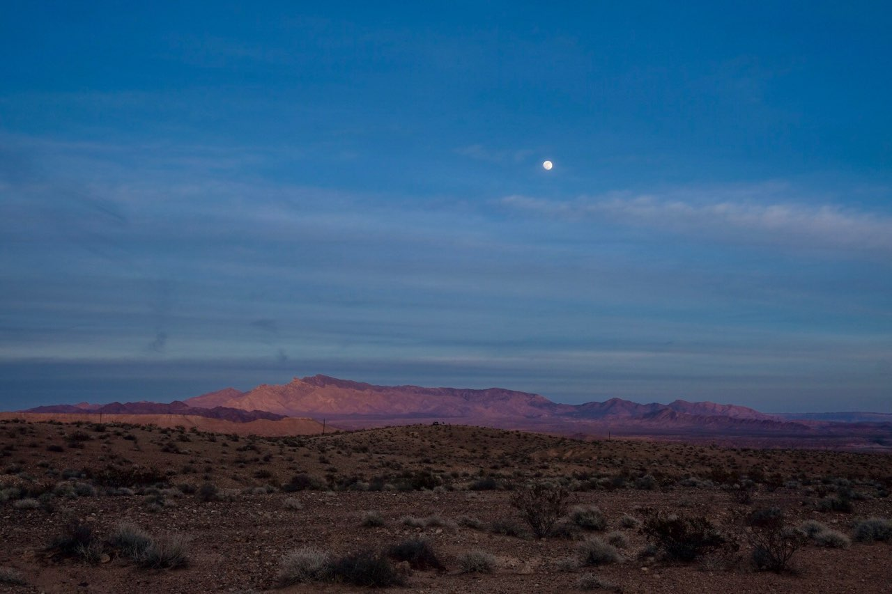 Virgin Mountains at sunset with a full-supermoon rising above