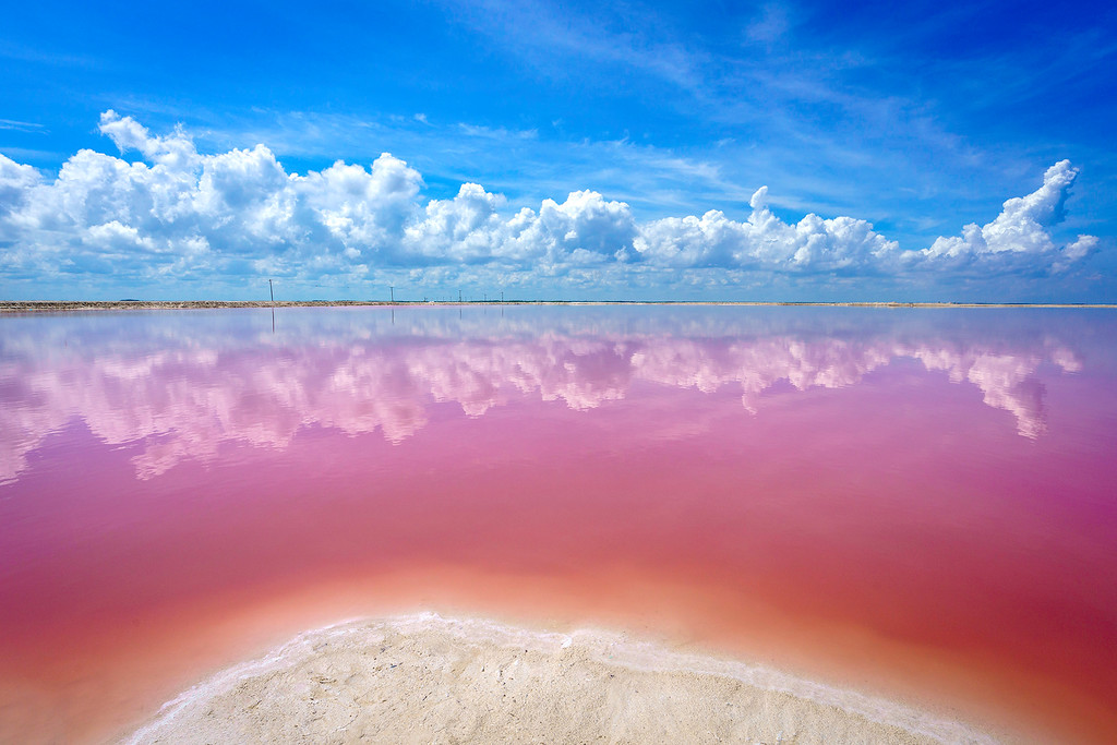 las coloradas - In a corner of the Ría Lagartos Biosphere Reserve, about 3 hours from Cancun, is a magical place where sea water turns bright pink!The Las Coloradas pink lakes are used for industrial-scale sea-salt production. As the water evaporates, salinity causes an explosion in the growth of red algae, plankton and brine shrimp, tinting the water reddish-pink. You may even spot some flamingos hanging out in the area too.