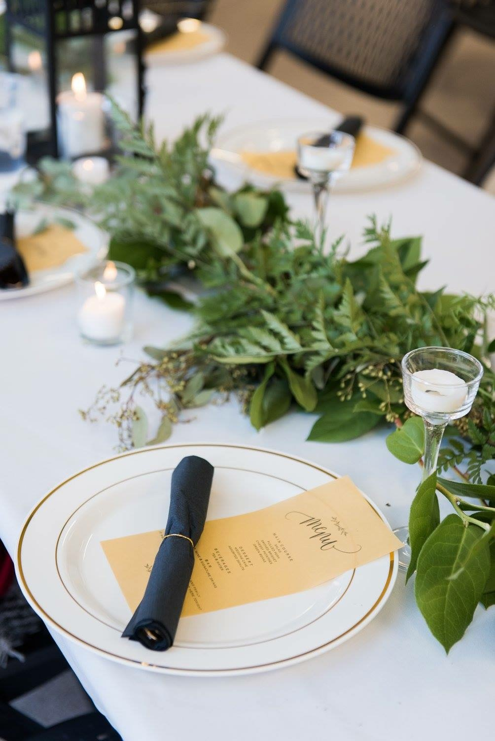 Winter wedding reception with mixed greenery and candle light, Anderson Building, Emporia, KS. Photo by Holli B Photography