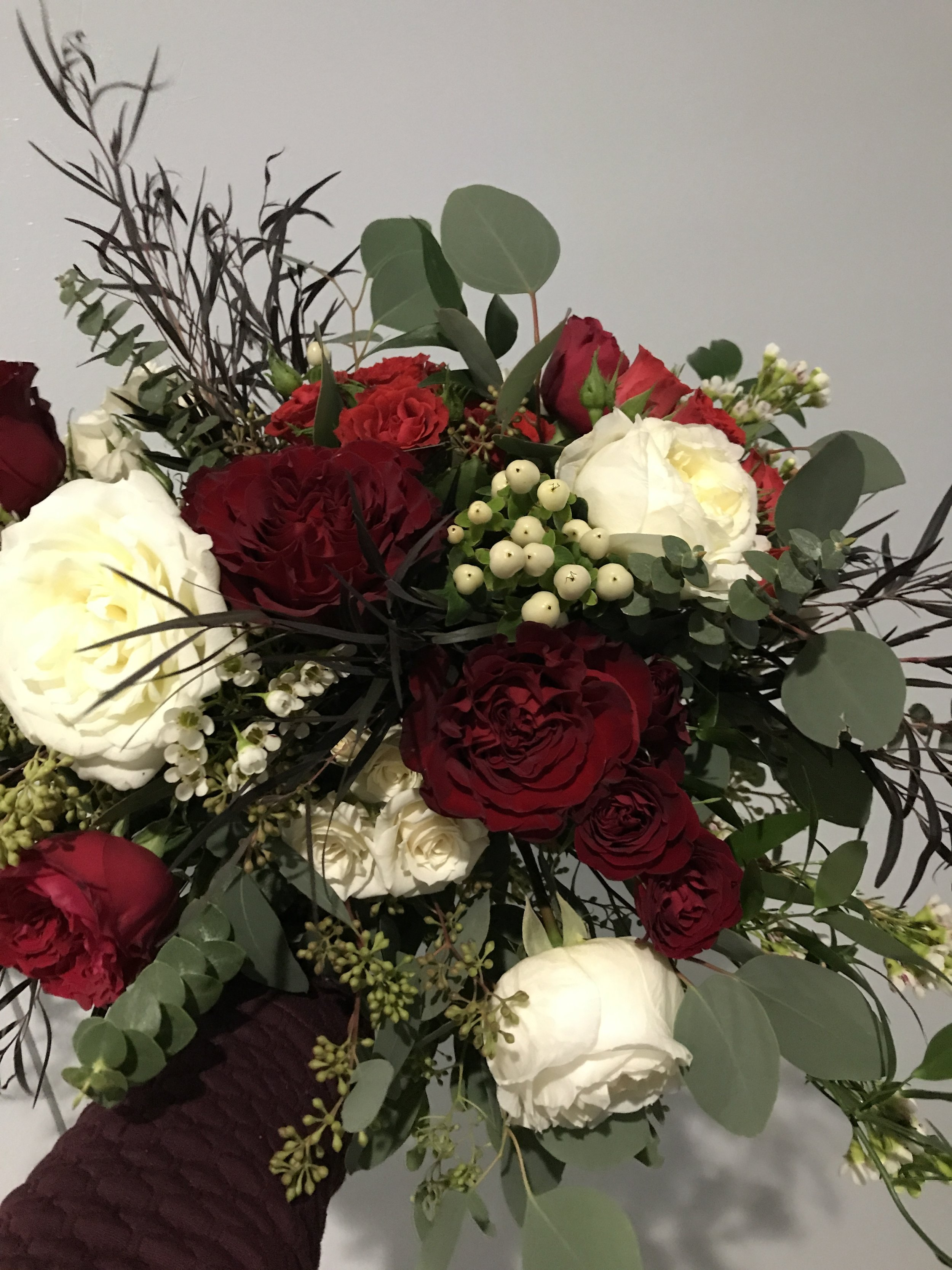 Late winter bouquet in burgundy and cream with berries