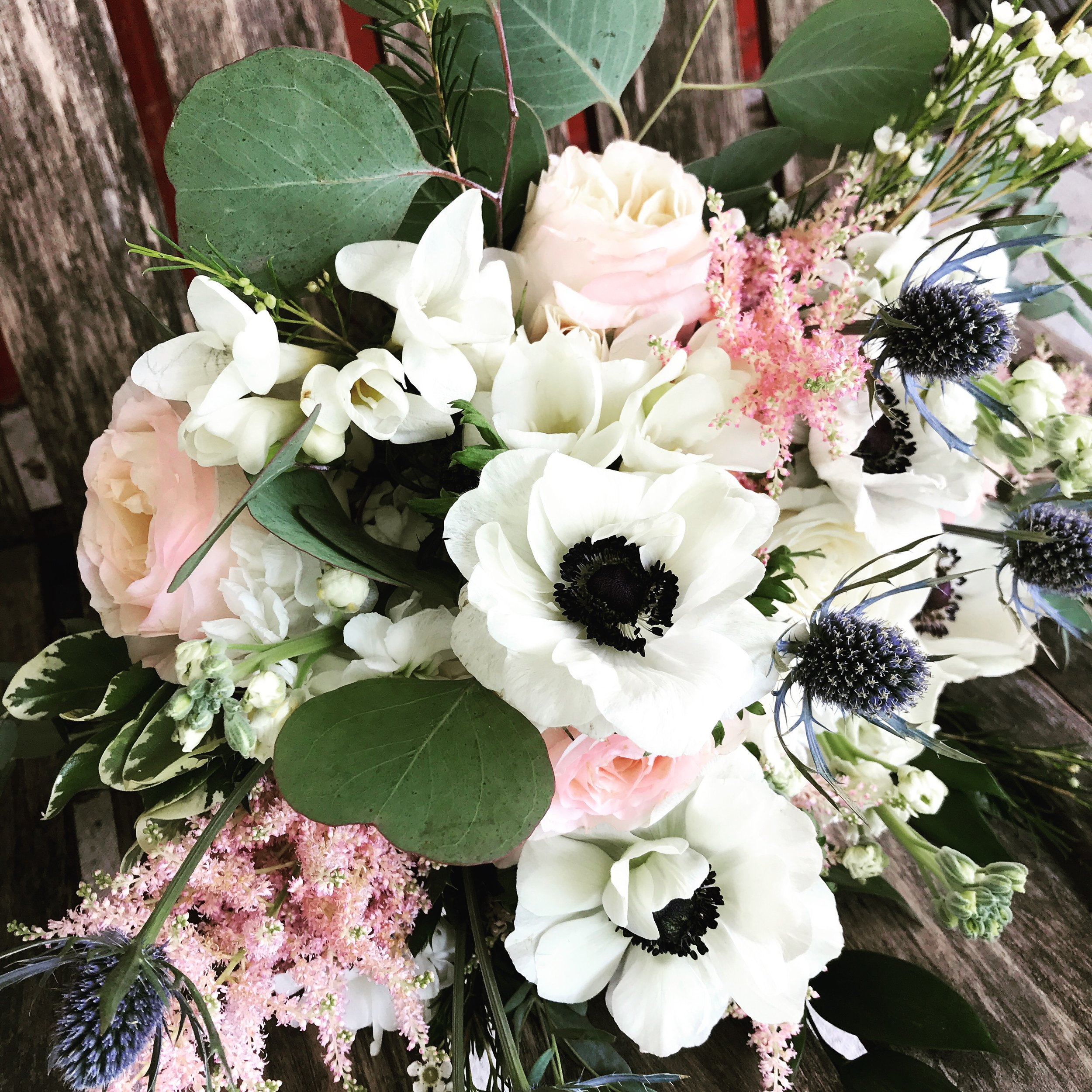 White anemones with blush roses and blue thistle
