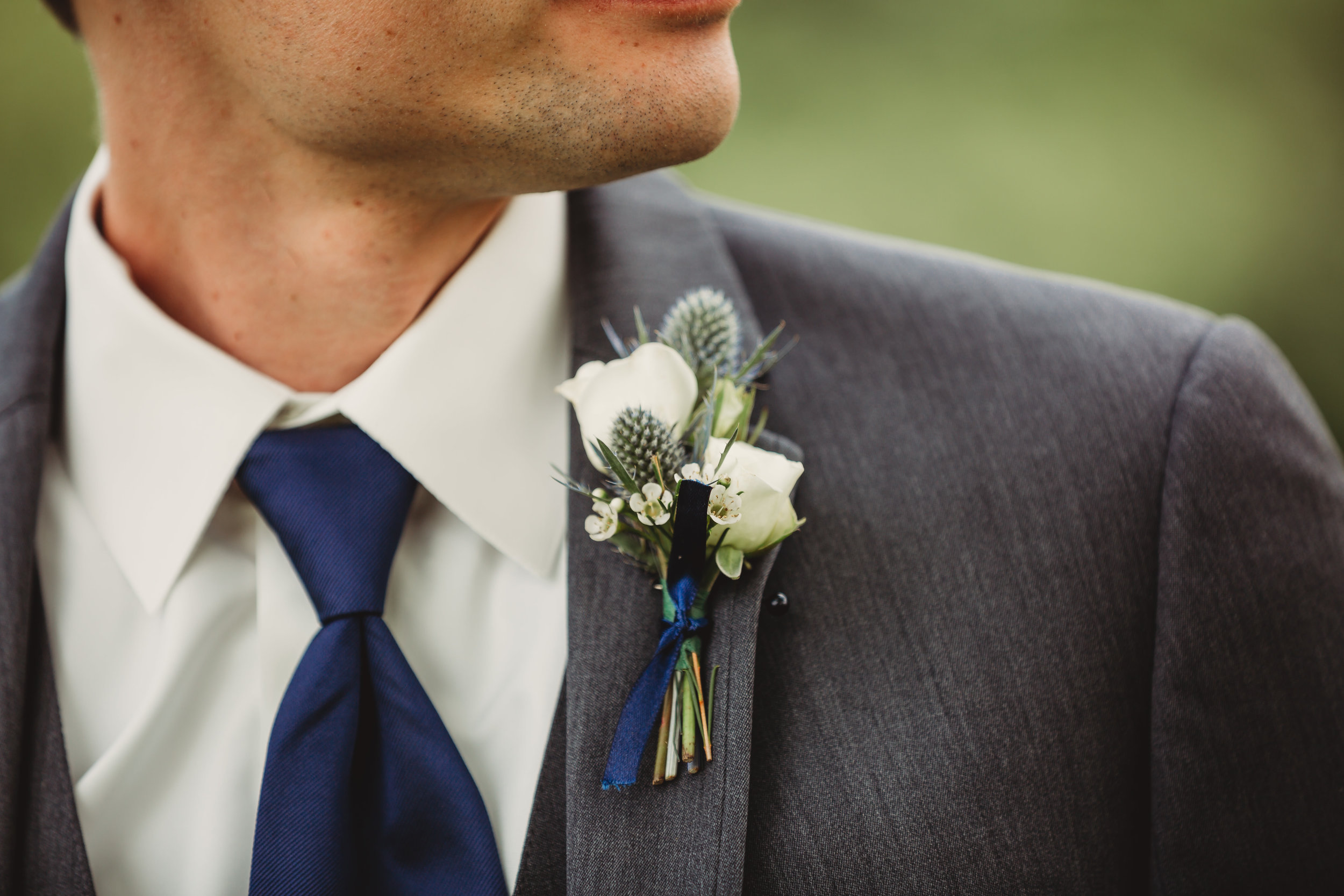 White boutonniere with blue thistle