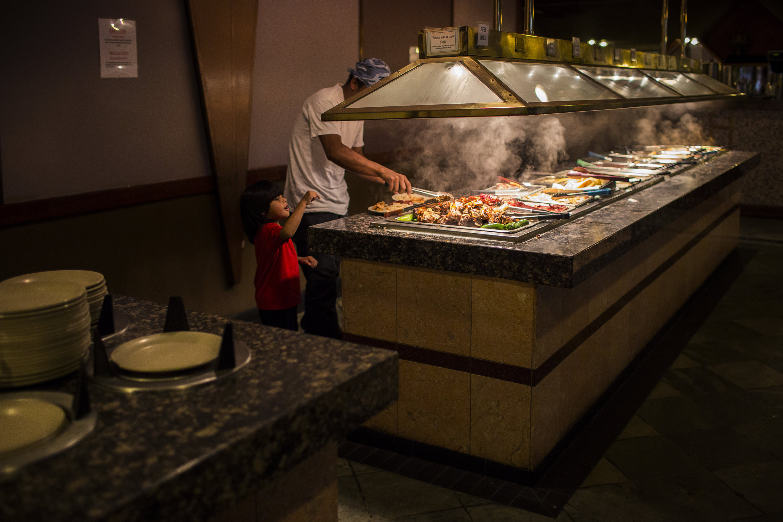 Dikeni serves himself and Fransuas food at a Chinese buffet, their first stop upon Dikeni and Fransuas' arrival in Houston on Jun. 10, 2017. Martin do Nascimento for The Texas Tribune.