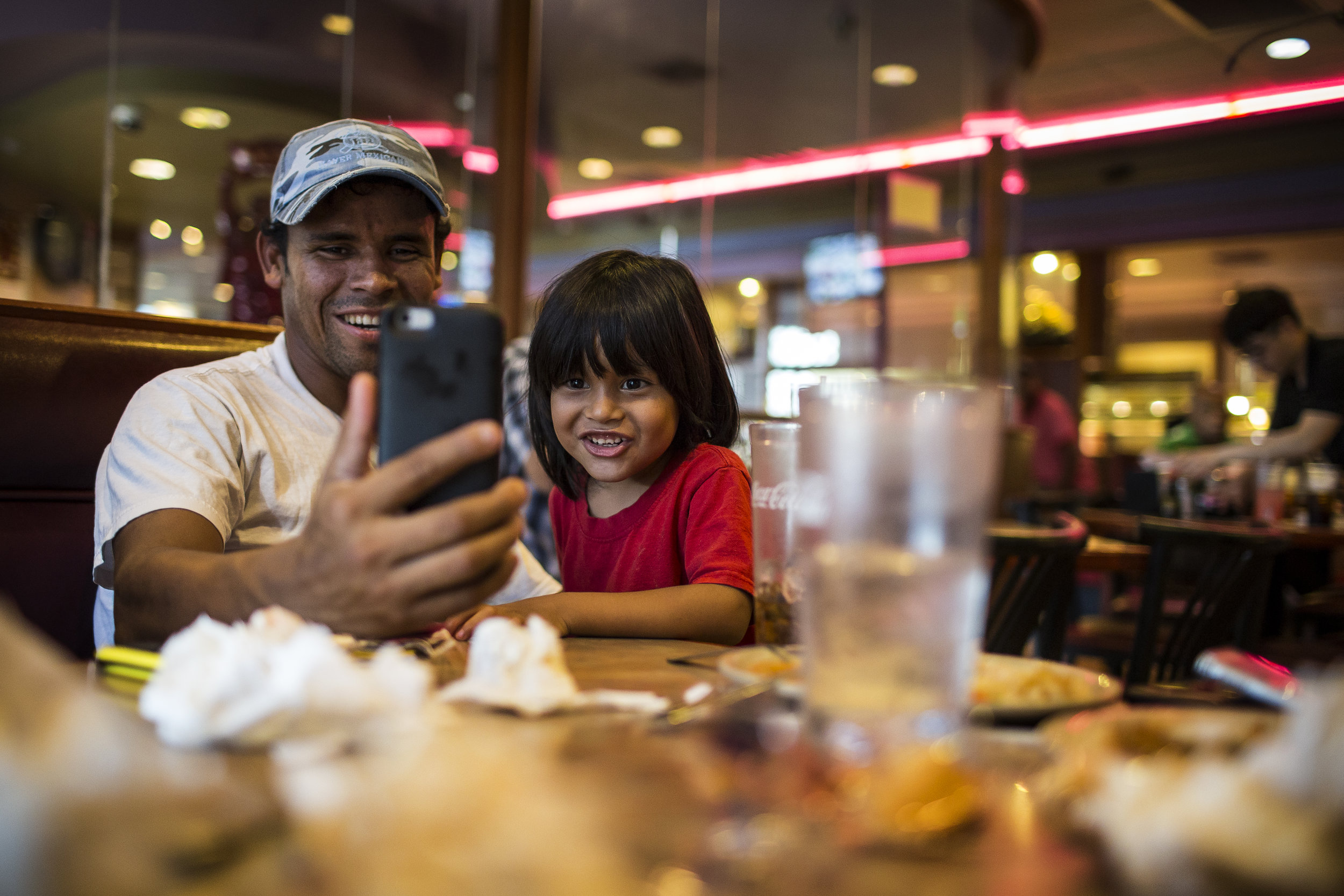 Dikeni and Fransuas (3) video-chat with Karina and Caleb (1), who are in Tijuana, from a Chinese buffet, their first stop upon their arrival in Houston on Jun. 10, 2017. Martin do Nascimento for The Texas Tribune.