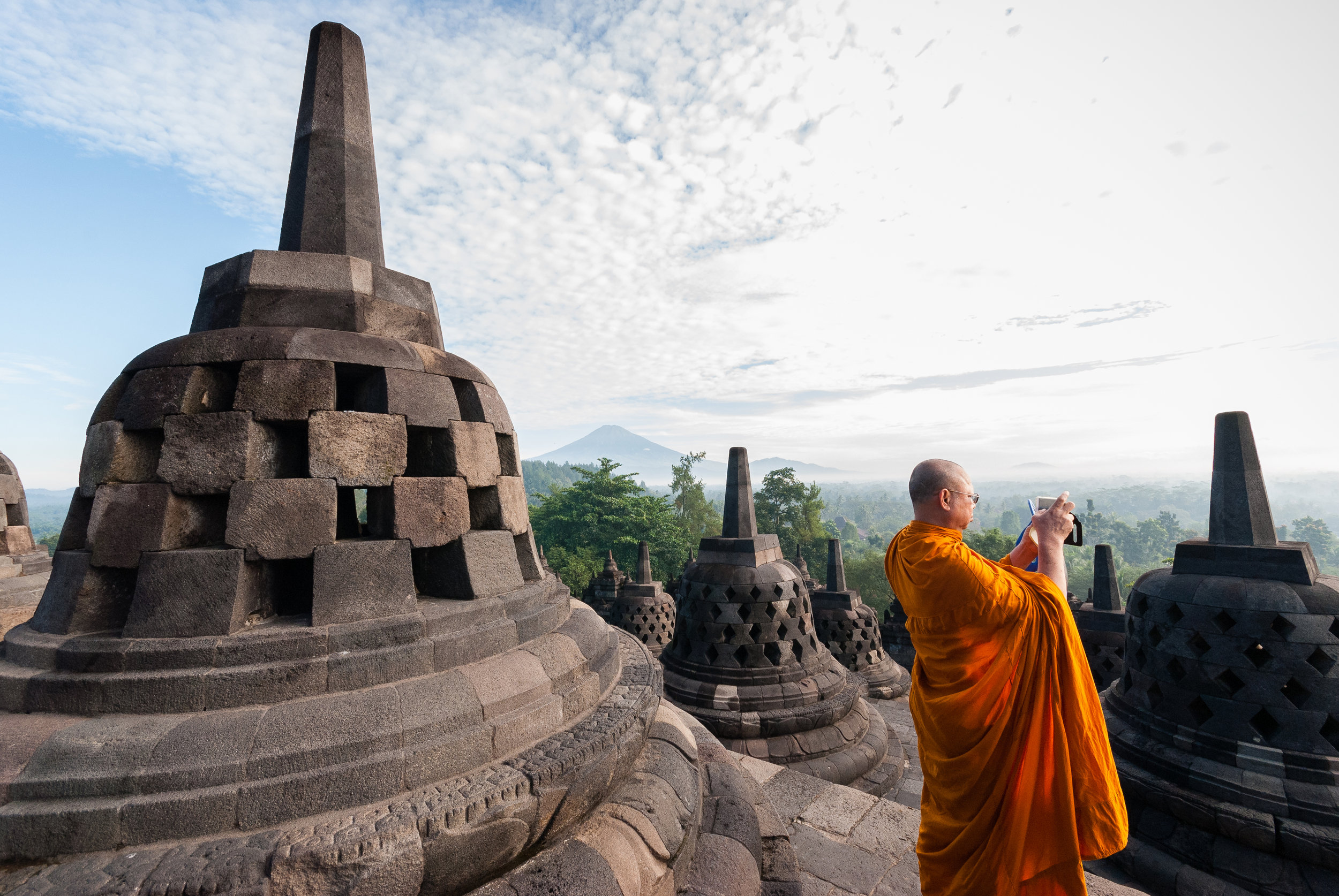 A monk enjoys the Borobudur view, the world's largest Buddhist temple. The temple is decorated with 2,672 relief panels and 504 Buddha statues. The central dome is surrounded by 72 Buddha statues, each seated inside a perforated stupa. Indonesia
