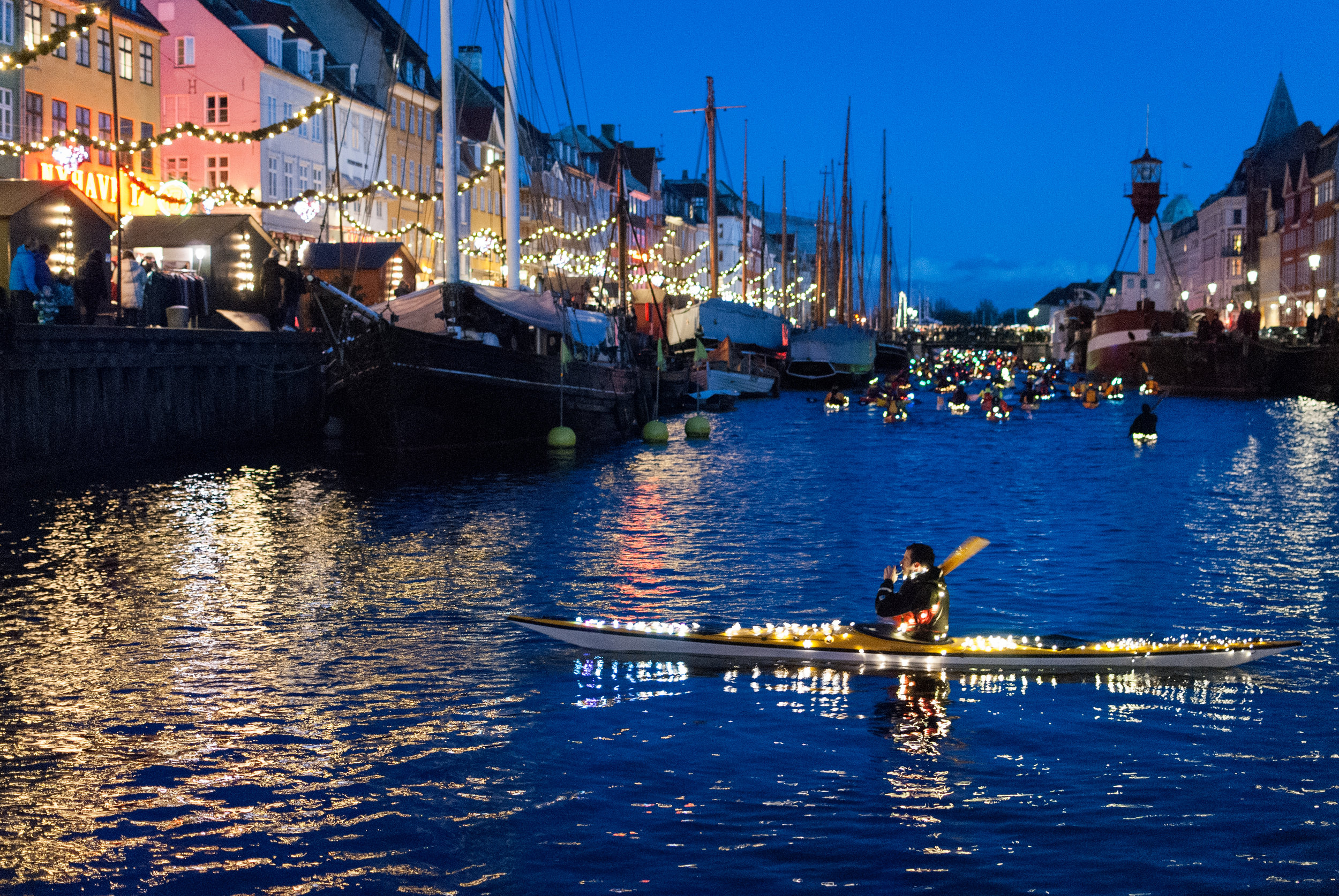 Hundreds of kayaks, each decked out with shimmering lights, sailed across the city's waters 13 December to the joyous musical accompaniment of Christmas carols. At every stop, parade participants and crowds gathered at the water's edge and sing to celebrate St Lucy's Day. Nyhavn, Copenhagen
