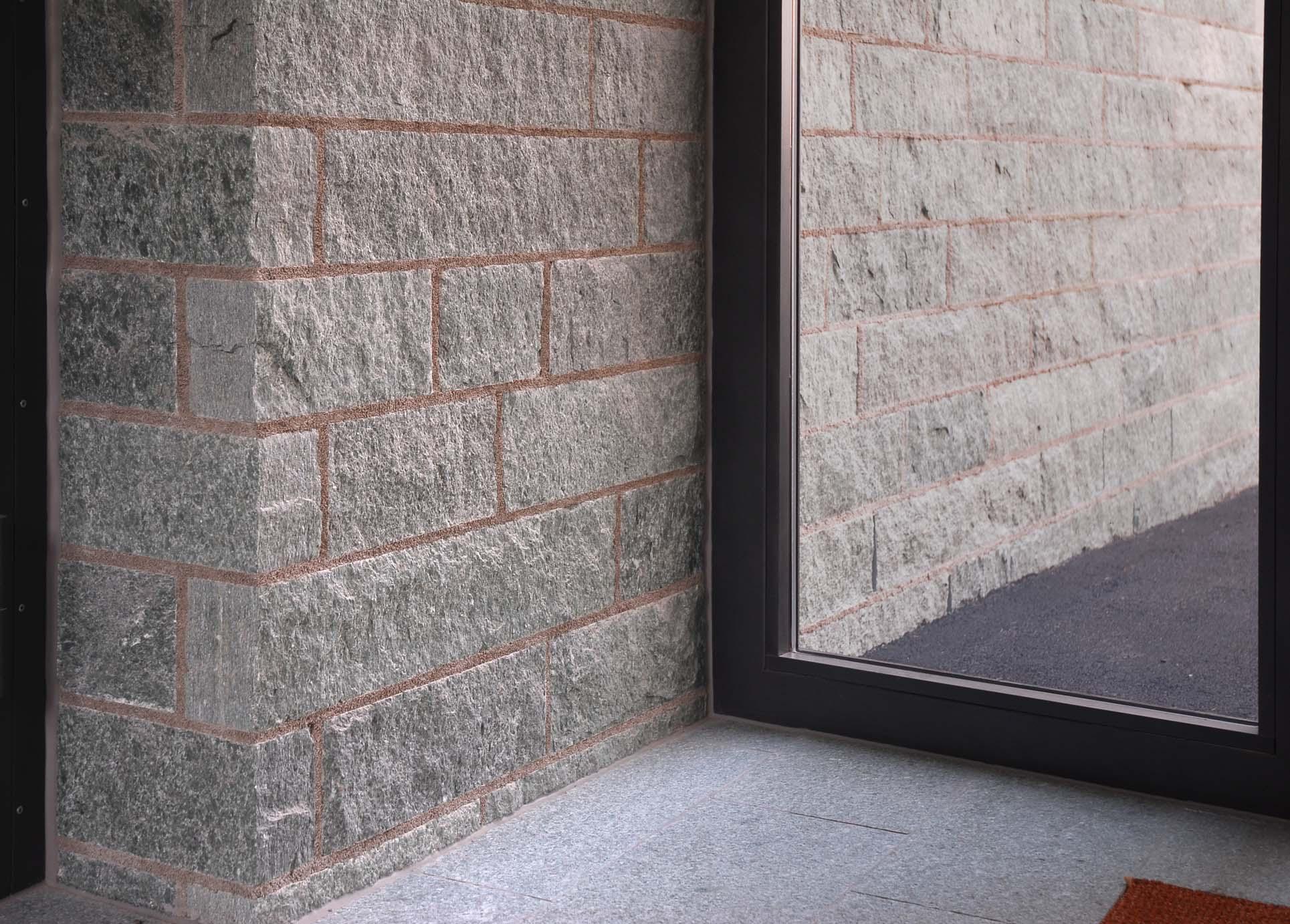 Die homogene Wirkung der Natursteinfassade überzeugt auch im Eingangsbereich.