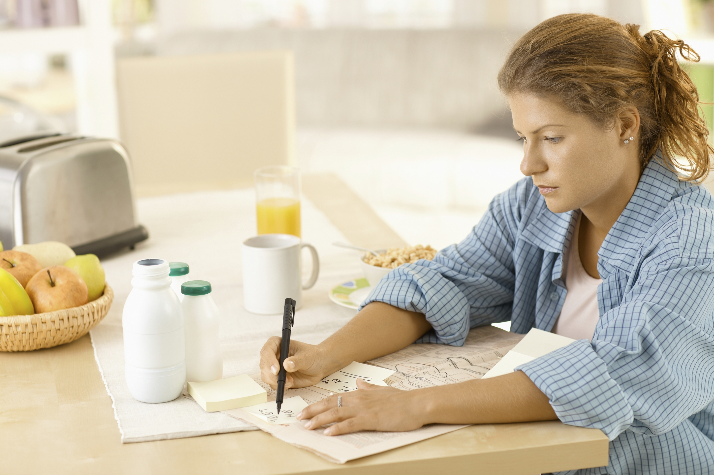 stock-photo-14658398-young-woman-writing-notes-in-kitchen.jpg