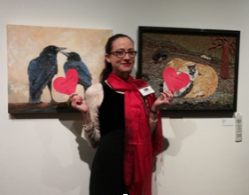 PAL Gallery Manager Stephanie Amon in front of Best Friends by LaRhee Webster, oil on canvas, and Paw Partners by Xuan My Ho, mosaic