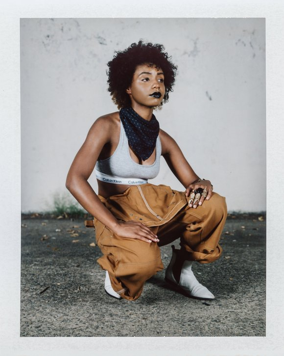 THIS EFFORTLESS ANDROGYNOUS look has a special place in my QTPOC heart. Bae is giving Rosie the Riveter a run for her money in the camel colored overalls, they are ready to work it. This is how you rock a sports bra people. Floridians take note.    #Winning combo : BLACK LIPS | SCARF | BOOTS