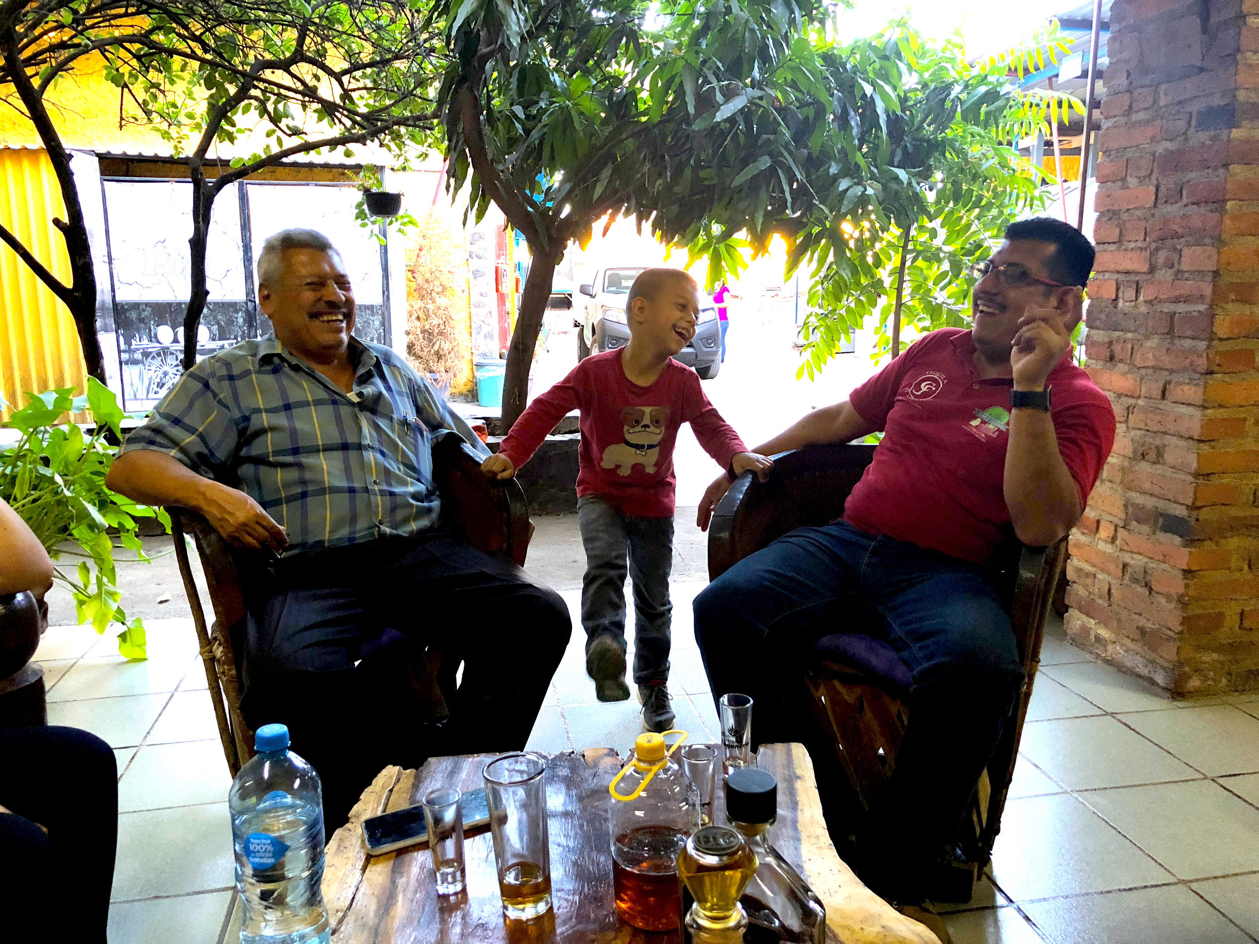 Three generations of the Correa family laughing and having fun at their small tequila distillery in Amatitan