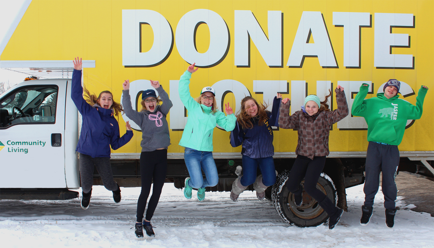 Children jumping in front of yellow truck