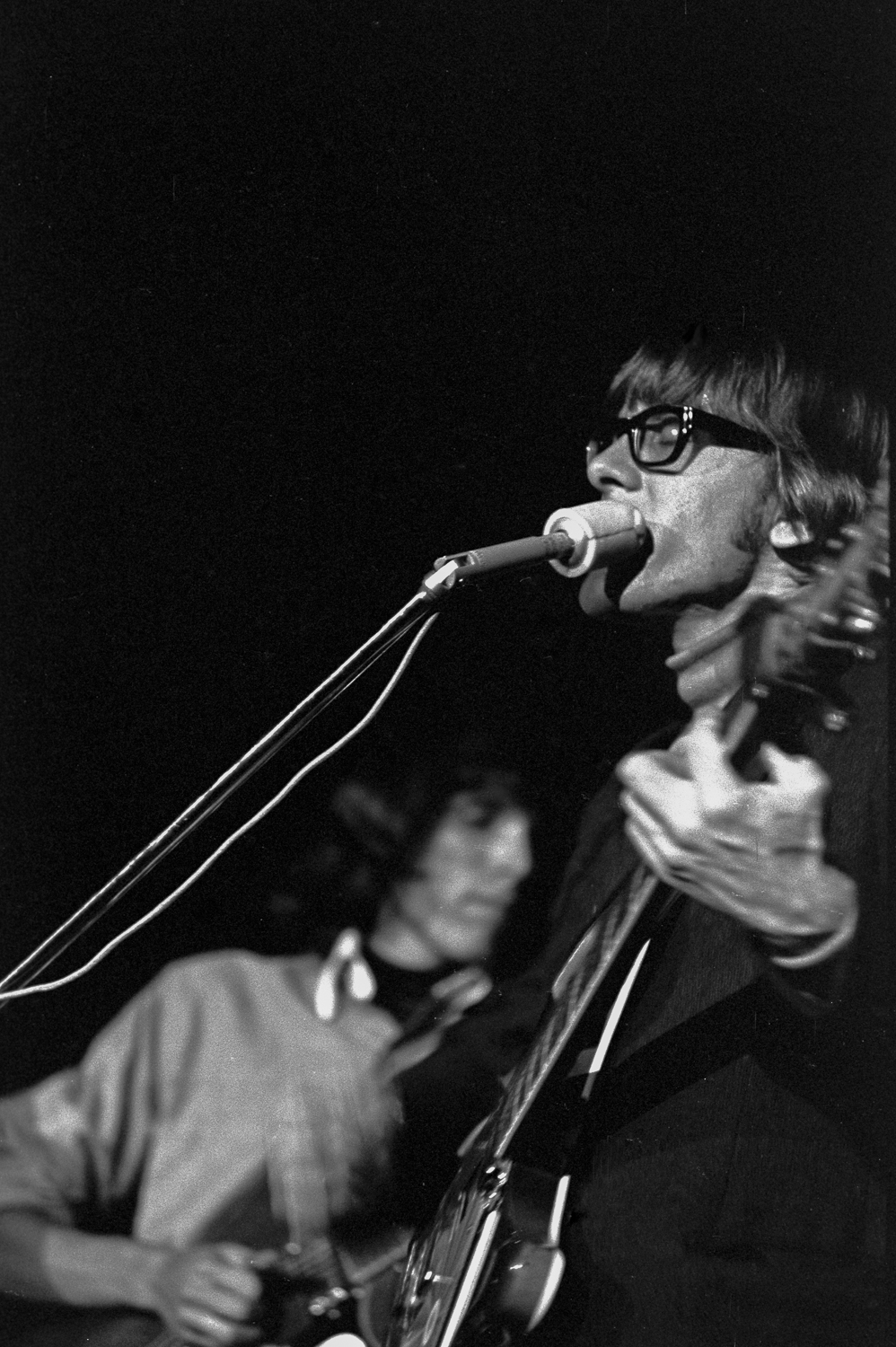 Paul Kantner (right) and Jorma Kaukonen (left) singing at a Stanford University concert, 1966