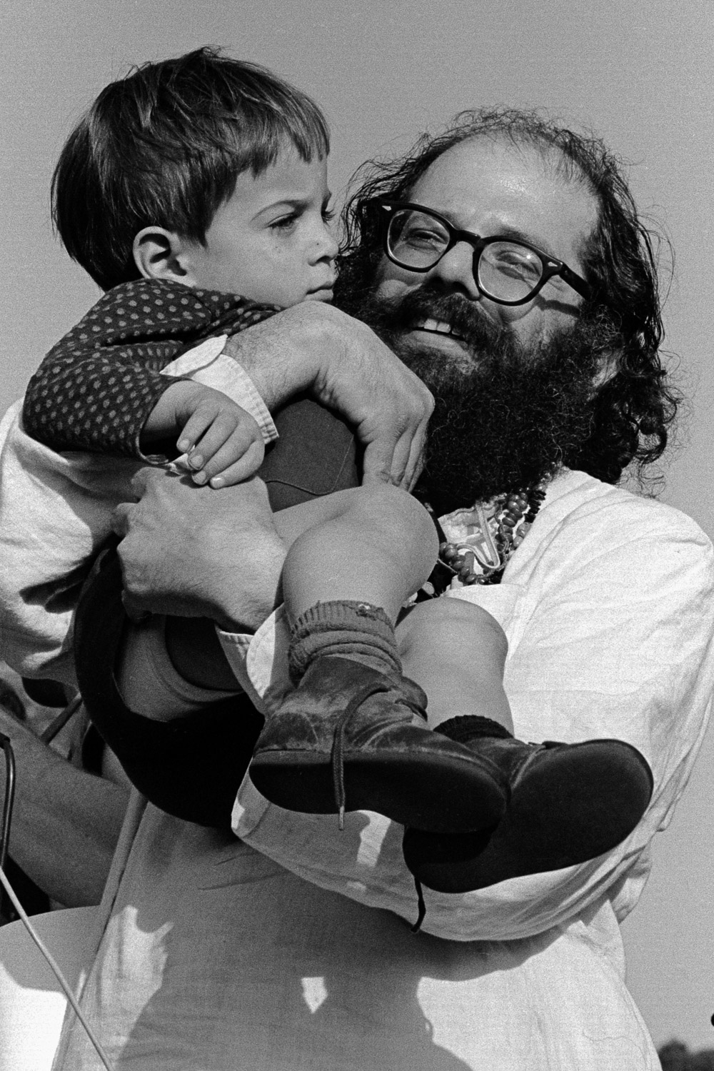 Allen Ginsberg  holds a child on the stage of the Human Be-In