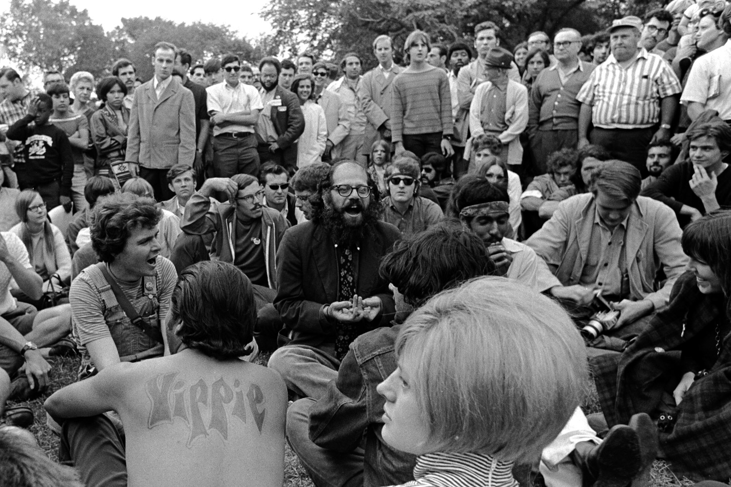 "Allen Ginsberg is chanting ""om"" in long, sustained breaths, joined by hundreds of participants from all walks of life."