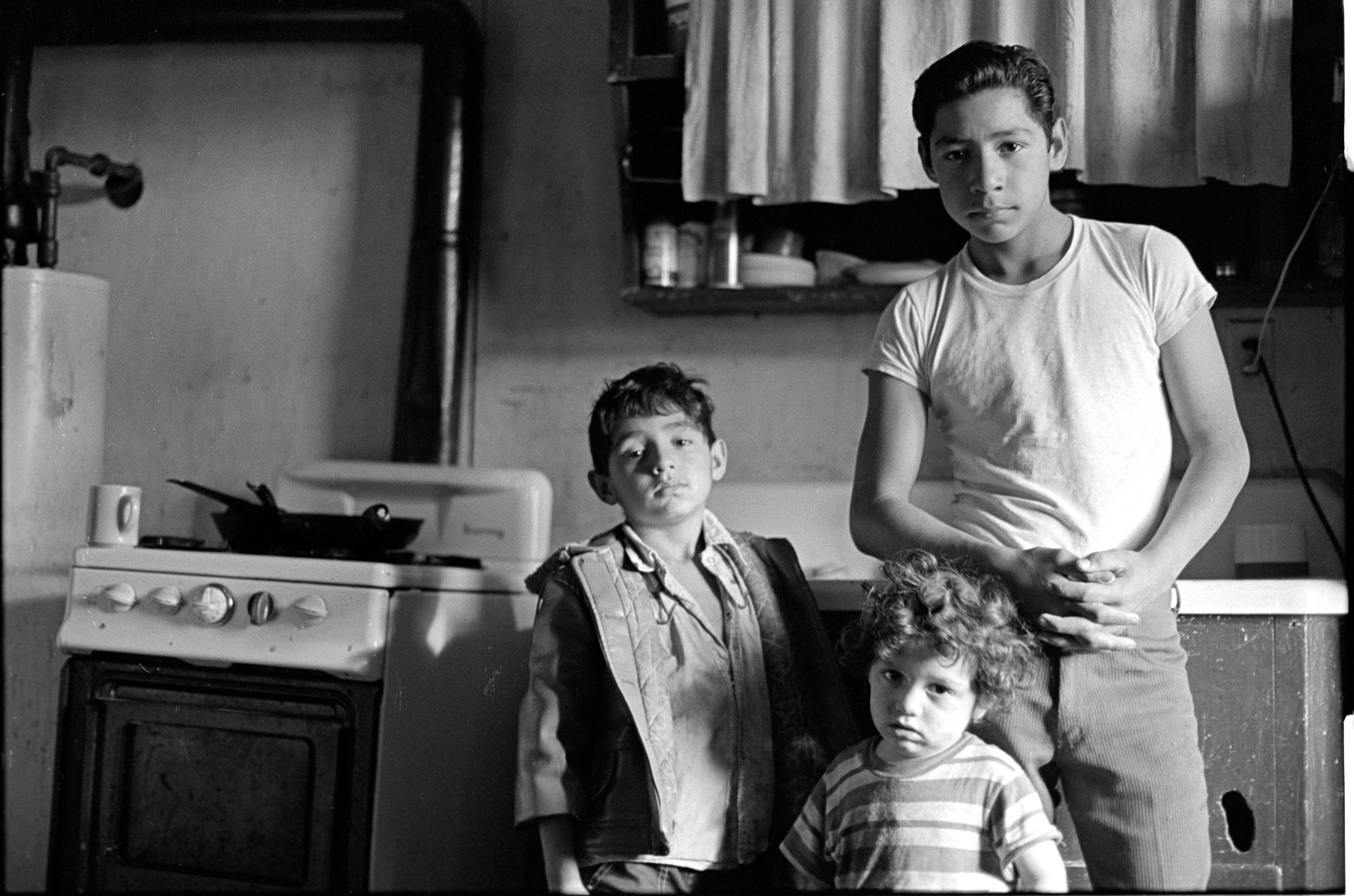 These three boys are the sons of farm workers in Watsonville, California. This is their kitchen.