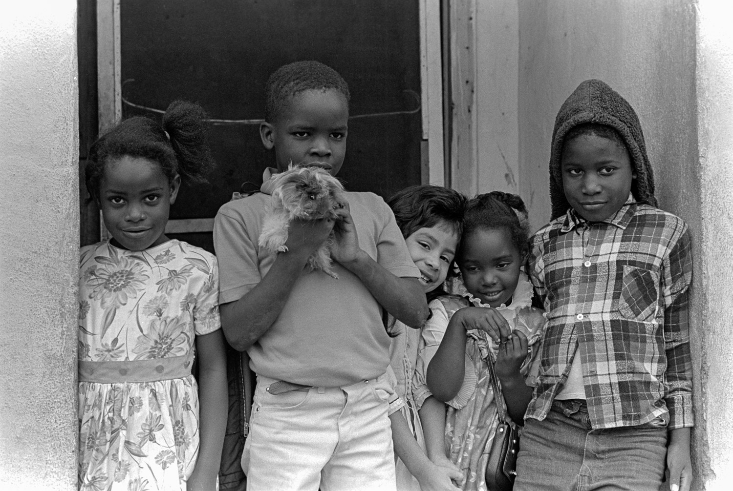 Five kids and a guinea pig in farm worker housing, Watsonville, California