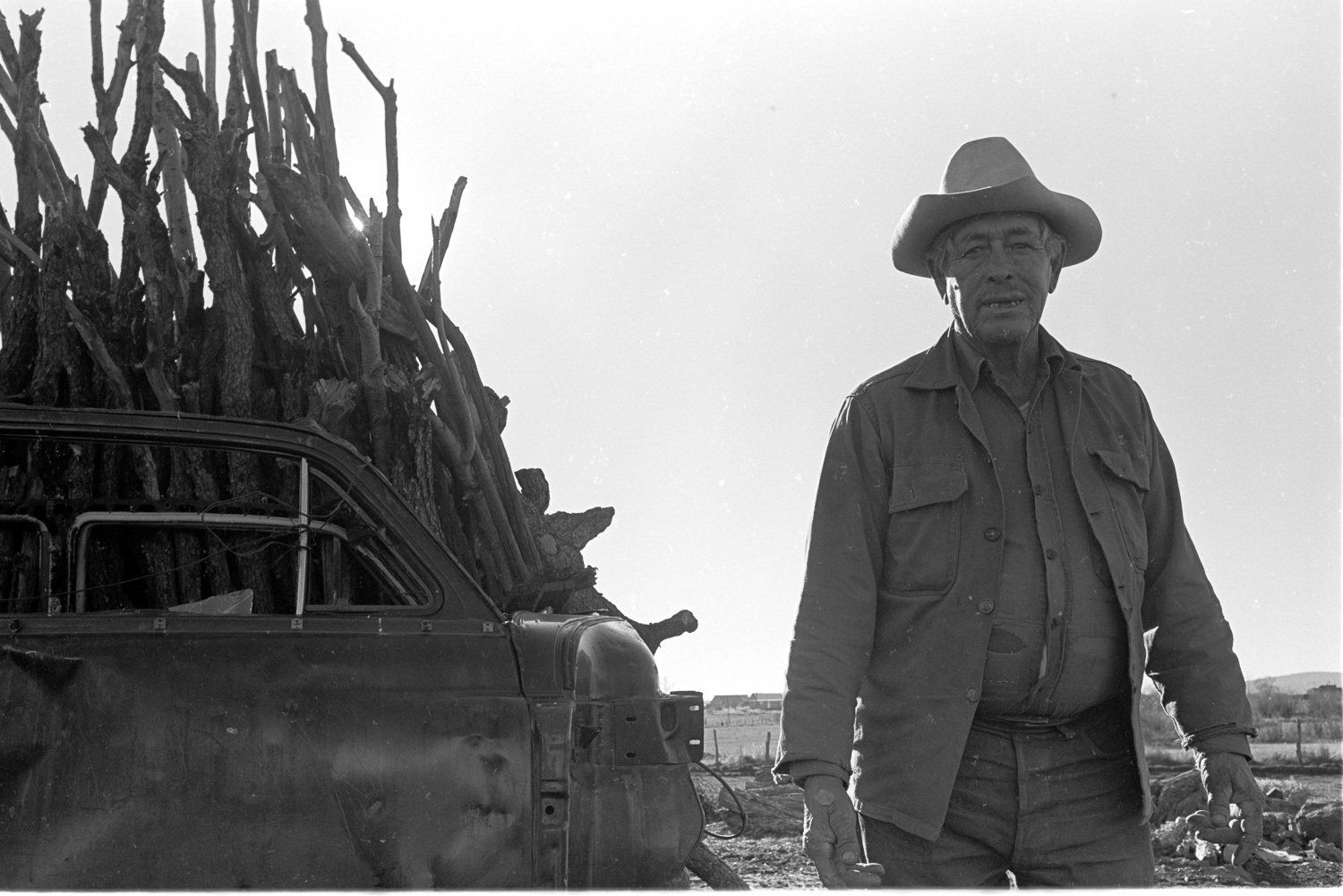 This farmer's face is as weather-beaten as the car door leaning against the stack of firewood.
