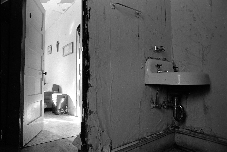 A well kept and brightly lit bedroom adjoins this dark bathroom in disrepair.
