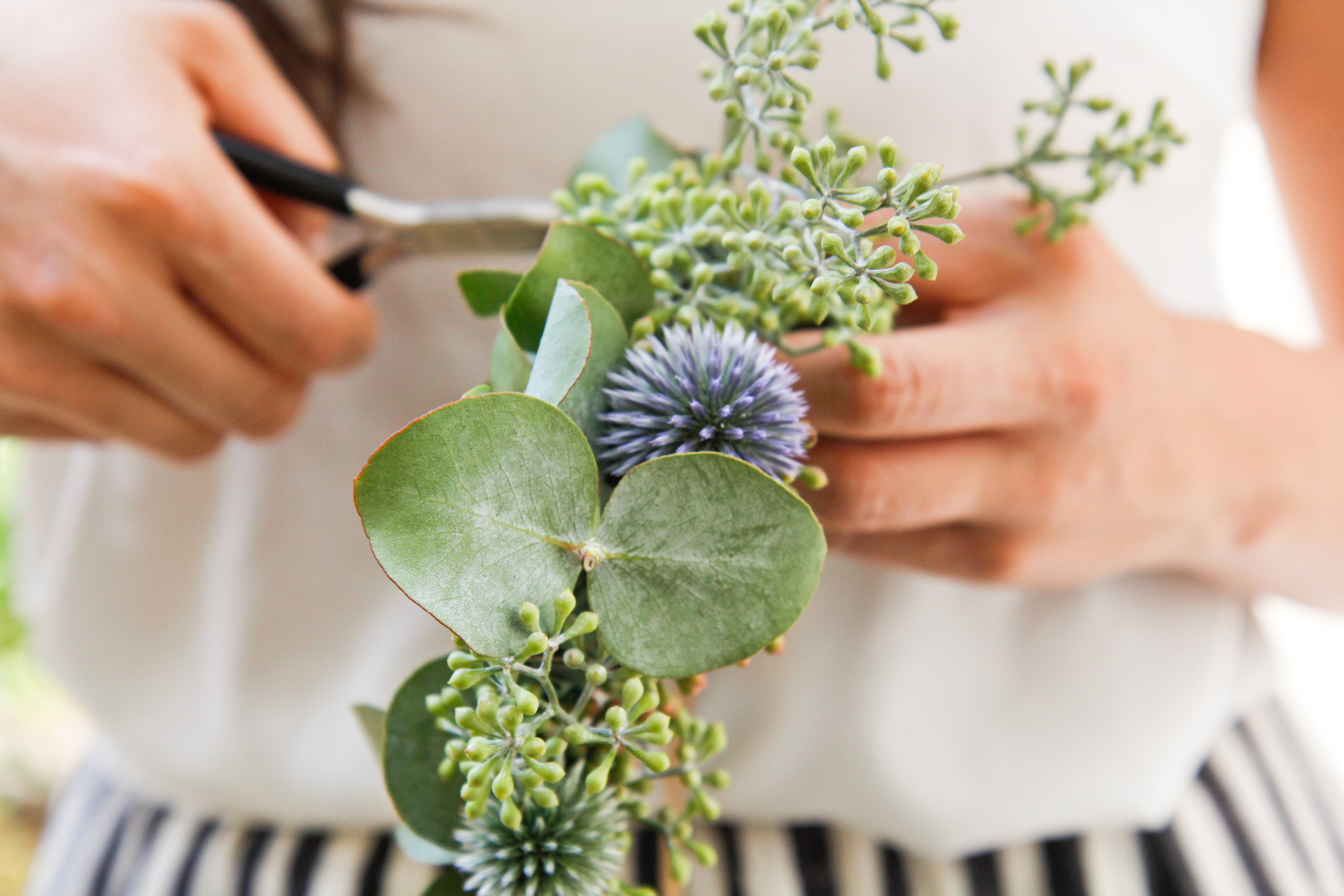 "Making a flower crown with the right kind of flora ensures that your design will look great throughout your entire event. This one is made from seeded Eucalyptus and globe thistle, which imbue it with the messages of ""spirituality"" and ""independence"", respectively, according to the language of flowers."
