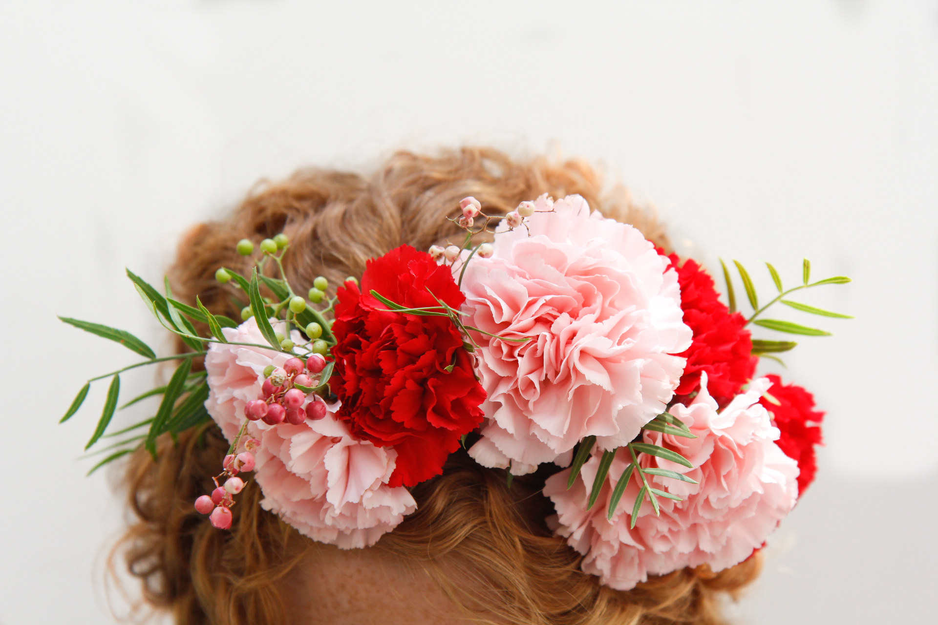 A crown made of carnations will last a long time but will look very different when dried. This crown is festive and fun with pink and red carnations and a bit of pink peppercorn.