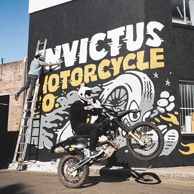 Process photo of the mural artwork going up at the new @sol_invictus_moto Alexandria service & showroom. Their signature tyre-man with some big rad lettering. Featuring @_adriankorner popping it up on one wheel.  Photo by @yeahradcreative. - www.sindysinn.com.au #sindysinn #solinvictus #mural #caferacer #doaflip