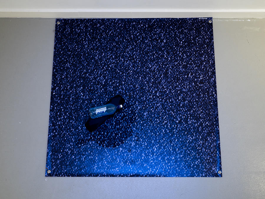 There is a real stink to the place; somewhere between bleach, Joop and cum. (Aerial View) 2016 Digital printed banner, found arm rest from cinema chair, pump water bottle, disinfectant.  120 x 120cm Photo: Luke Thompson
