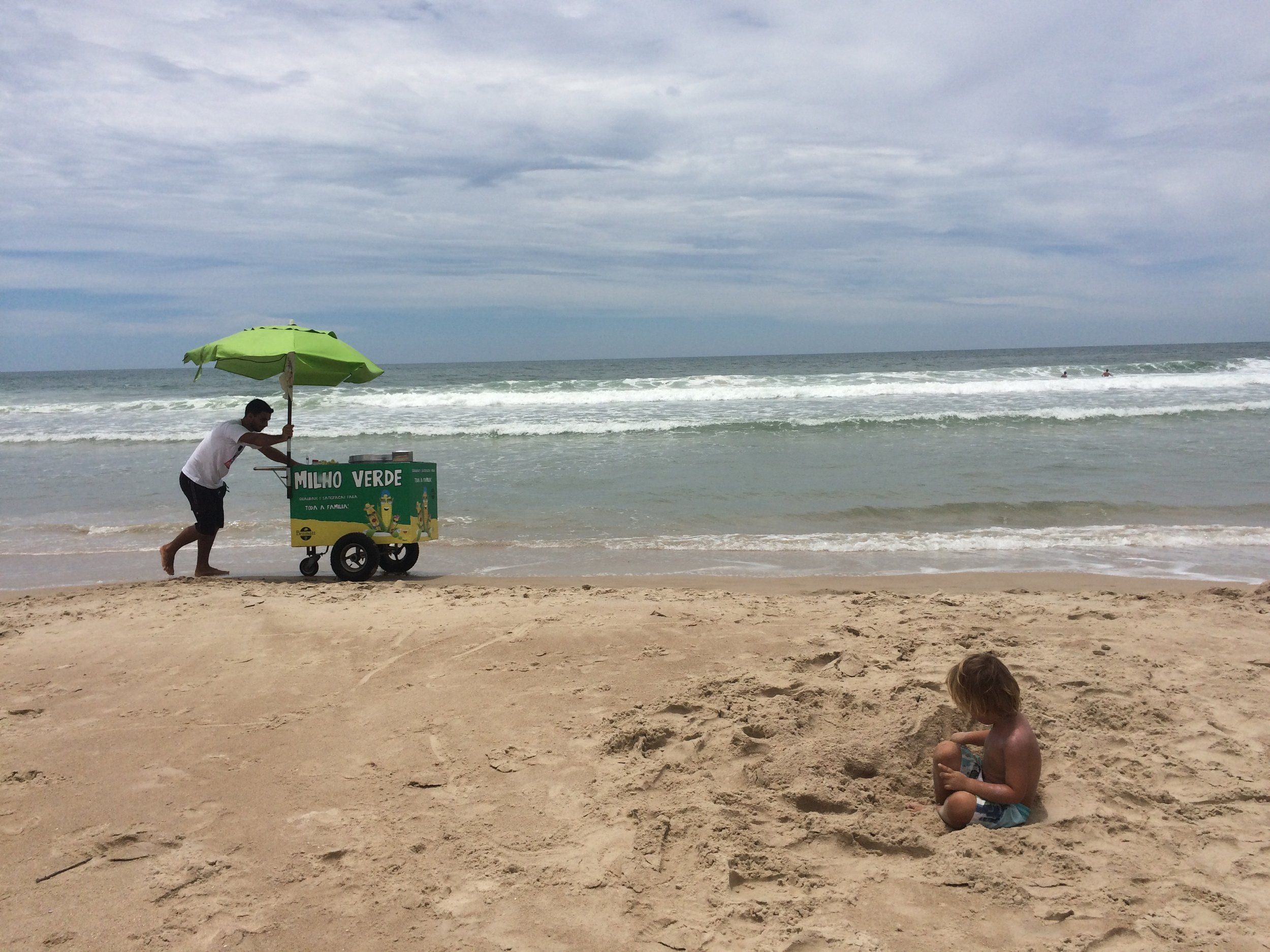 hugo loves the sand he could play in the sand all day. the man on the beach is selling corn which is amazing because they don't do that any were else in the world