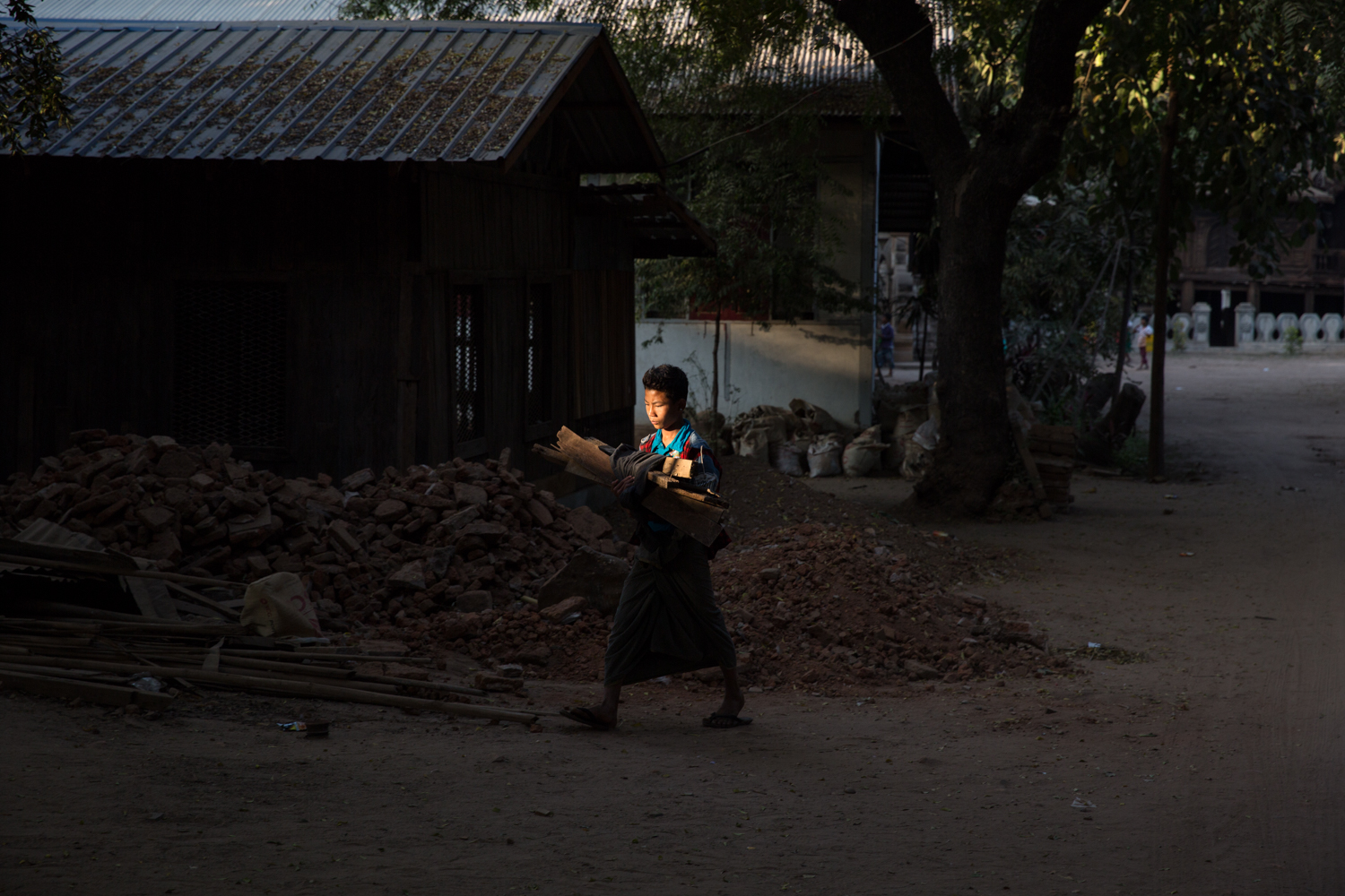 A boy carries firewood through a lonely sliver of light back to his home in Bagan, Myanmar.