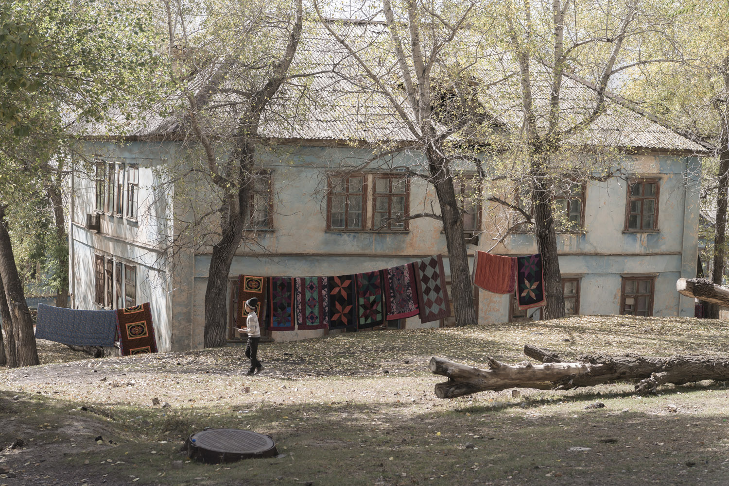 min-kush-soviet-uranium-mining-town-industrial-Russia-Kyrgyzstan-ruins-soviet-sign-jo-kearney-photos-video-photography-child-washing-blankets-drying.jpg