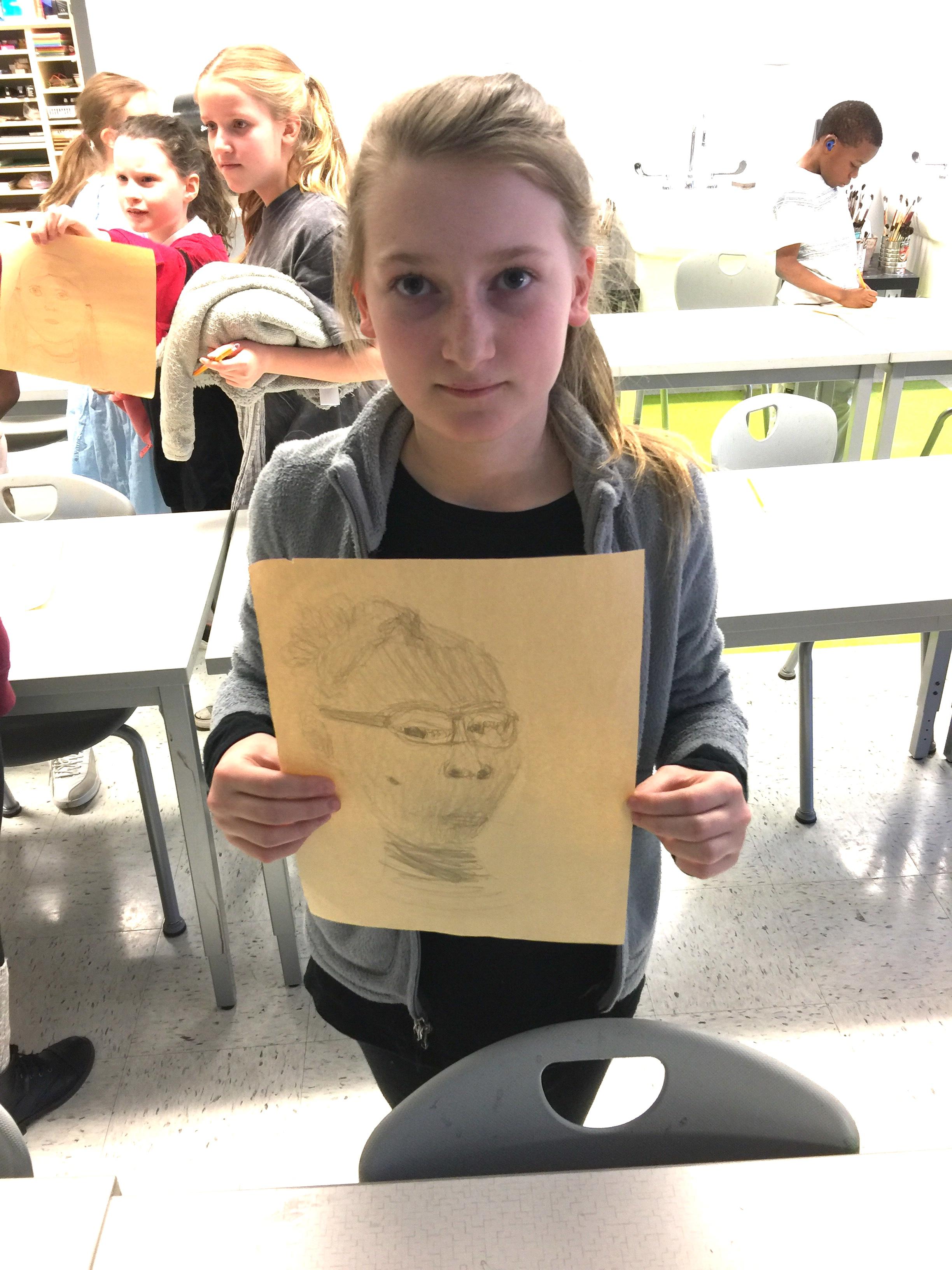 Ruby Calkin, holding the portrait she drew of her friend Lorelei.